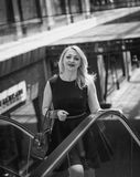 Black and white portrait of beautiful woman posing on escalator Royalty Free Stock Photography
