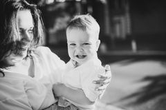 Black and white portrait. Beautiful young mom and cheerful adorable blond boy are playing, having fun. Woman love her son. Royalty Free Stock Images