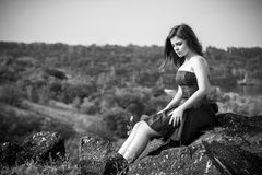 Black and white portrait of beautiful young sad brunette woman. Wearing elegant dress, sitting on the cliff above the river Stock Photo