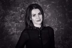Black and white portrait of beautiful young smiling  brunette woman. Wearing black blouse, standing behind dark background Royalty Free Stock Images