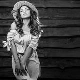 Black-white portrait of beautiful young woman in classic hat against old wooden wall Royalty Free Stock Photo