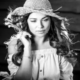 Black-white portrait of beautiful young woman in classic hat against old wooden wall Stock Images