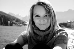 Black and white portrait of blond woman smiling looking camera in front of lake and moutnains Stock Image