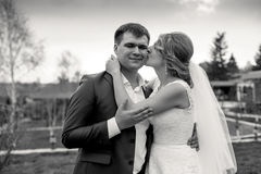 Black and white portrait of bride giving a kiss on grooms cheek Stock Images