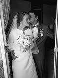 Black and white portrait of bride and groom kissing at hotel roo Stock Photos