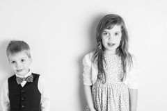 Black and white portrait of brother and sister standing against a wall Stock Photo