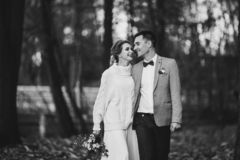 Portrait of happy newlywed couple walking in forest.