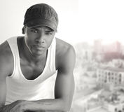 Black and white portrait. Portrait of a cool young man leaning on chair in white tank and trendy cap Stock Photo