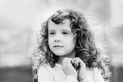 Black and white portrait of a curly little girl. Royalty Free Stock Image