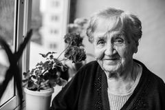 Portrait of an elderly woman on the balcony. Black and white portrait of an elderly woman on the balcony royalty free stock images