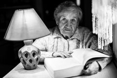 Portrait of an elderly woman reading a book in the night light. Black and white portrait of an elderly woman reading a book in the night light Stock Photography