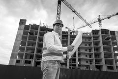 Black and white portrait of engineer with blueprints on building royalty free stock image