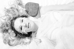 Black and white portrait of enjoying young pretty lady laying on white bed Stock Photos