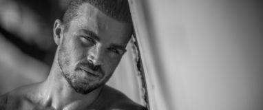 Handsome Caucasian Male Model posing in black and white portrait. Black and white portrait of fashionable white tanned male model posing on the beach and leaning royalty free stock images