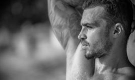 Handsome Caucasian Male Model posing in black and white portrait. Black and white portrait of fashionable white tanned male model posing on the beach and leaning stock photos
