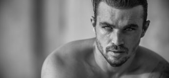 Handsome Caucasian Male Model posing in black and white portrait. Black and white portrait of fashionable white tanned male model posing on the beach stock photography
