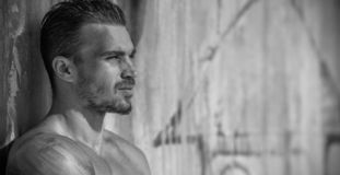 Handsome Caucasian Male Model posing in black and white portrait. Black and white portrait of fashionable white tanned male model posing on the beach and leaning royalty free stock photo