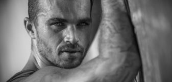 Handsome Caucasian Male Model posing in black and white portrait. Black and white portrait of fashionable white tanned male model posing on the beach and leaning royalty free stock photos
