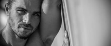 Handsome Caucasian Male Model posing in black and white portrait. Black and white portrait of fashionable white tanned male model posing on the beach and leaning royalty free stock photography