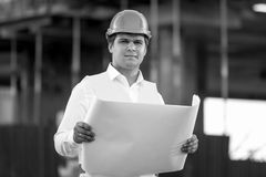 Black and white portrait of foreman posing with documents and bl Stock Image