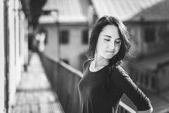 Black and white portrait of a girl. Black and white portrait of brunette attractive girl in dress at the wooden balcony of old building. With perspective. Soft Royalty Free Stock Image