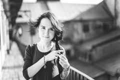 Black and white portrait of a girl. Black and white portrait of brunette attractive girl making her hair at the wooden balcony of old building. With perspective Stock Photography