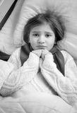 Black and white portrait of girl with flu lying in bed Stock Images