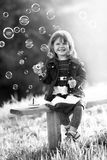 Black-and-white portrait of a girl sitting on a wooden bench blo Royalty Free Stock Photos
