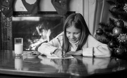 Black and white portrait of girl writing letter to Santa at livi Royalty Free Stock Image