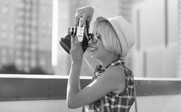Black and white portrait of hipster girl using retro film camera Royalty Free Stock Photography