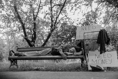 Black and white portrait of homeless man lying on bench. Stock Images