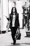 Black and white portrait of a Italian Woman. A young beautiful dark hair woman with a handbag walking with intent in the beautiful narrow streets of Genoa, an royalty free stock images