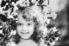 Black and white portrait of a little girl with spring flowers in Stock Photo
