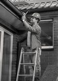 Black and white portrait of male carpenter repairing house roof stock image