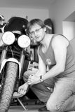 Black and white portrait of man with bike. In garage royalty free stock photos