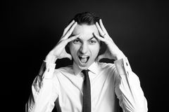 Black and white portrait of a man in a white shirt, screaming at the camera, hands on head royalty free stock image