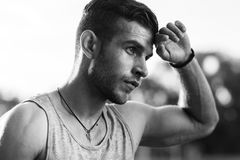 Black-and-white portrait of man wiping sweat after workout Stock Photography