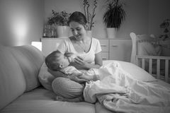 Black and white portrait of mother feeding her baby at night fro Stock Photos