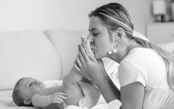 Black and white portrait of young mother kissing her baby son`s feet. Black and white portrait of mother kissing her baby son`s feet Royalty Free Stock Photography