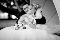 Black and white portrait newly bride lying on groom knees Stock Photos