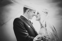 Black and white portrait of newly married couple.wind lifting up long veil Stock Photos