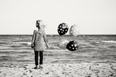Pensive teenager white Caucasian child kid with bunch of balloons standing on beach