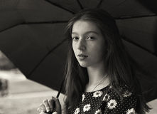 Black and white portrait of a pretty girl with freckled. Standing under umbrella Stock Image