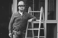 Black and white portrait of professional worker posing with ladder Royalty Free Stock Images