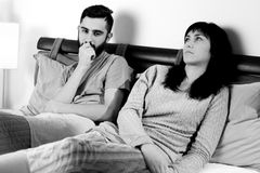 Black and white portrait of sad couple in bed after fight not talking royalty free stock photography
