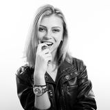 Black and white portrait of sexi young blonde lady. Sexy young blonde woman in leather jacket posing happy smiling over isolated copy space background, black and Stock Image