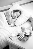 Black and white portrait of sick girl sleeping in bed at home Stock Photography