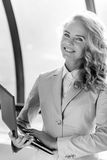 Black and white portrait of smiling business woman holding laptop. Black and white indoor portrait of successful business woman holding laptop and smiling royalty free stock photos