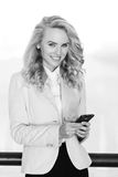 Black and white portrait of smiling woman using mobile phone. Black and white portrait of beautiful smiling woman with wavy hair using mobile phone. Model Stock Images