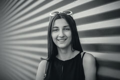 Black and white portrait of stylish happy young beautiful hipster woman against metal urban background Stock Photo
